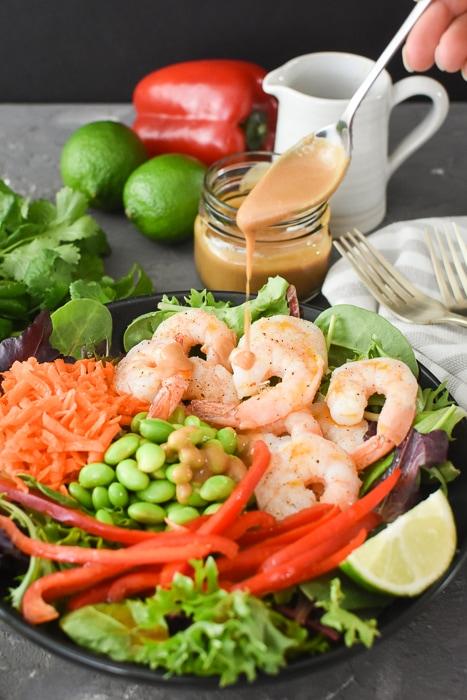 drizzling peanut sauce on a spicy thai shrimp salad