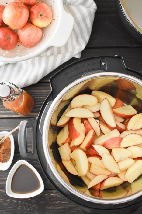 apples in an Instant Pot with spices, cider and maple syrup on the side