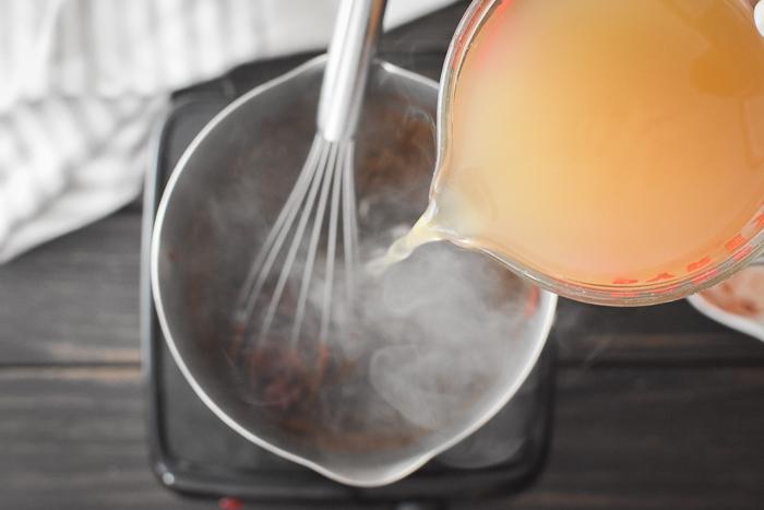 Adding broth to a pot