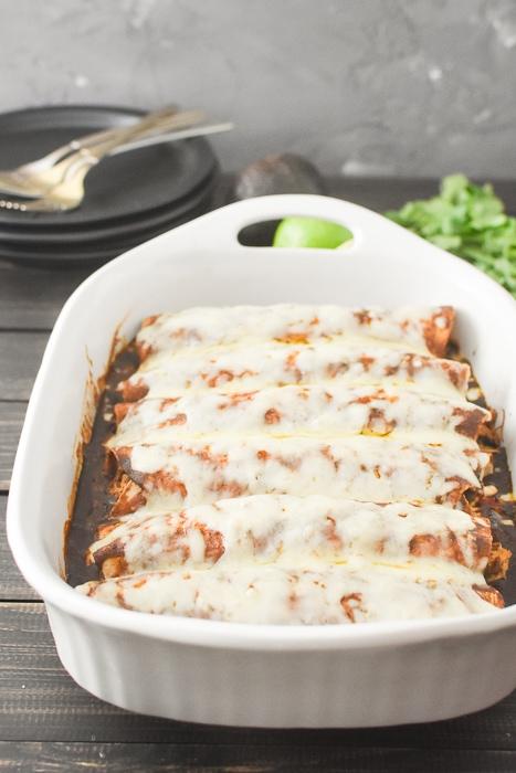 A white baking dish full of cheesy enchiladas
