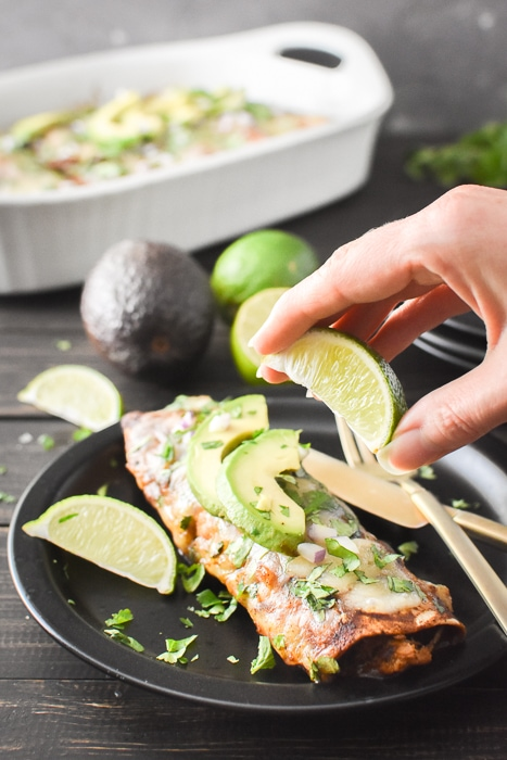 squeezing a lime wedge over an enchilada