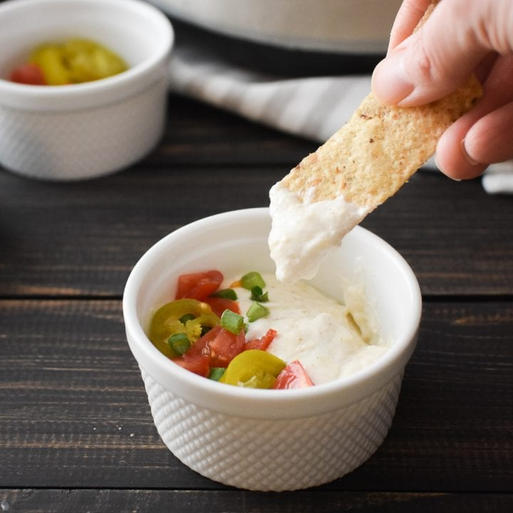 a tortilla chip being dipped in queso