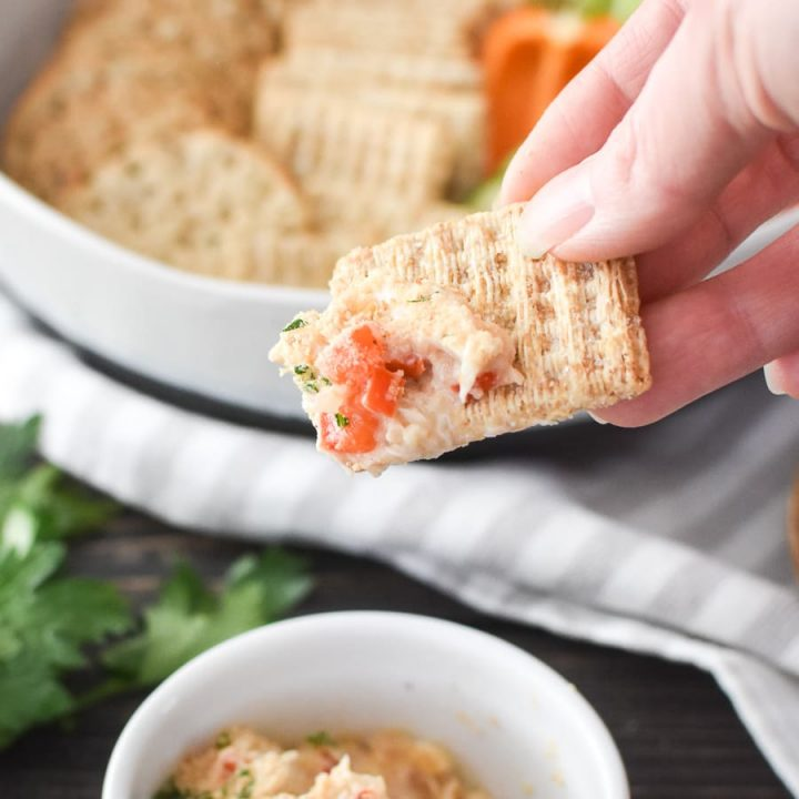 A cracker being dipped into crab cake dip