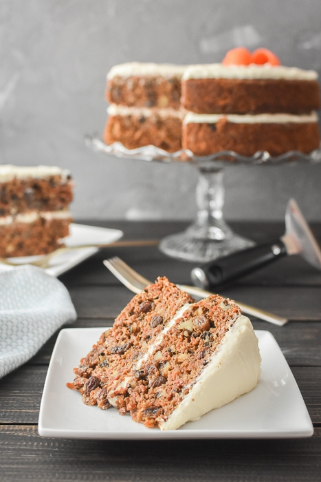 a slice of carrot cake in front of a full cake in the background