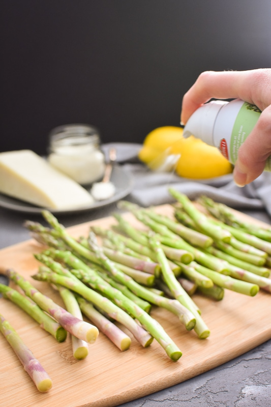 spraying olive oil on asparagus