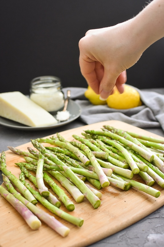 salt and pepper being sprinkled on asparagus
