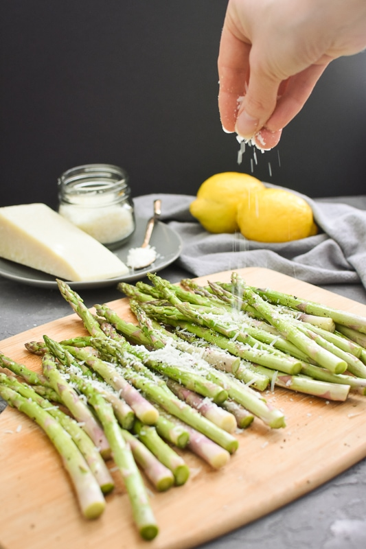 pecorino being sprinkled on asparagus