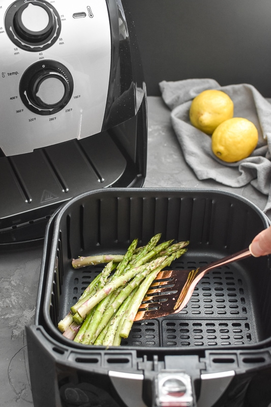 asparagus in an air fryer being turned with a spatula