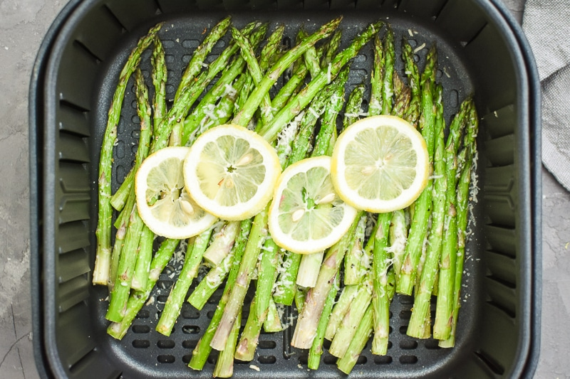 asparagus with lemons in an air fryer basket