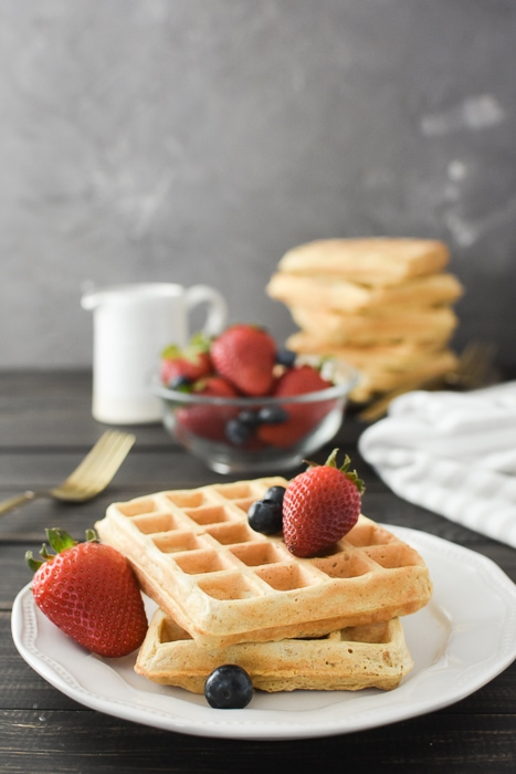 a stack of waffles with berries on top