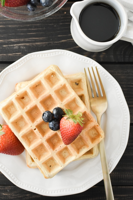 2 waffles with berries on a white plate