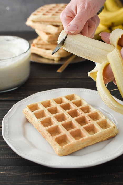 slicing a banana over a plain waffle