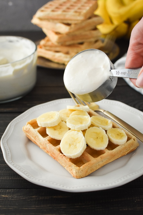 pouring pudding topping over a waffle covered in banana slices