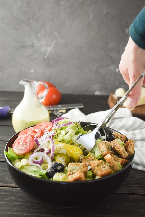 mixing an olive garden salad with salad tongs