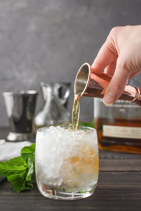 pouring bourbon into a glass of crushed ice