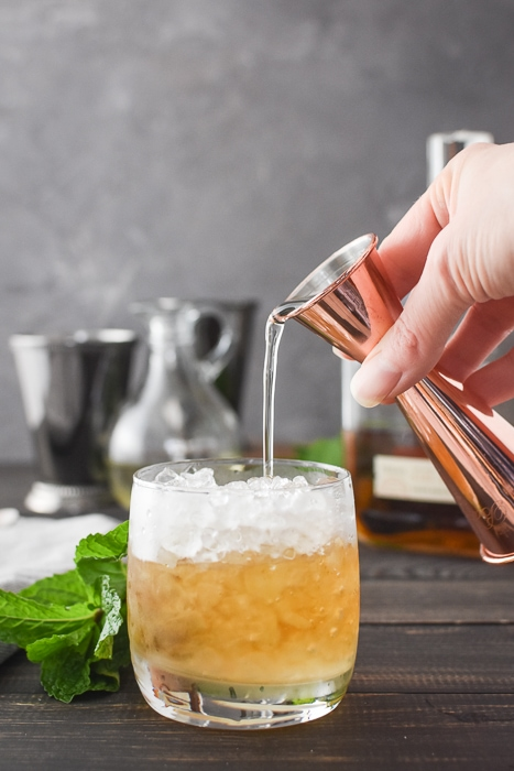 pouring simple syrup into a mint julep