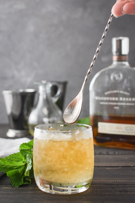 a mint julep about to be stirred with a copper barspoon