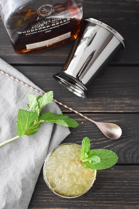 a mint julep with a bottle of bourbon and a julep cup