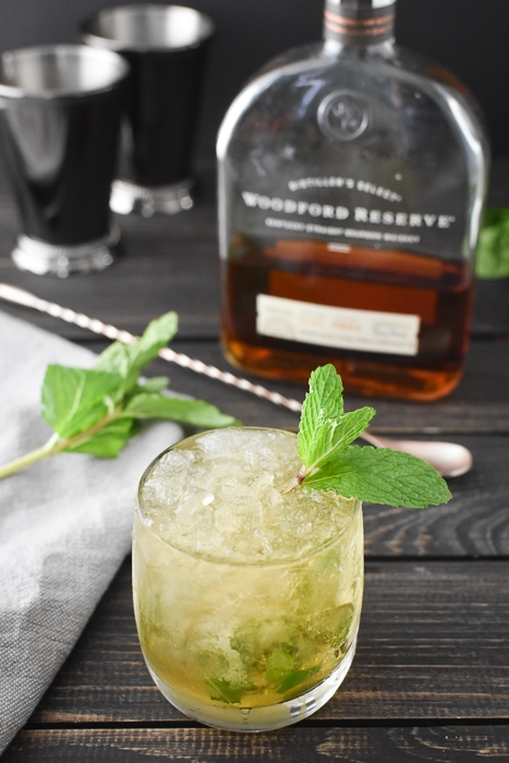 a mint julep with a bottle of bourbon and two julep cups