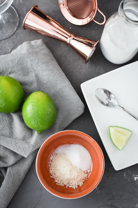 a small bowl that has sugar and shredded coconut next to 2 limes and a plate